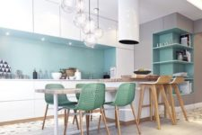 23 a chic kitchen with white cabinets and blue backsplash, green chairs and eye-catchy bubble pendant lamps
