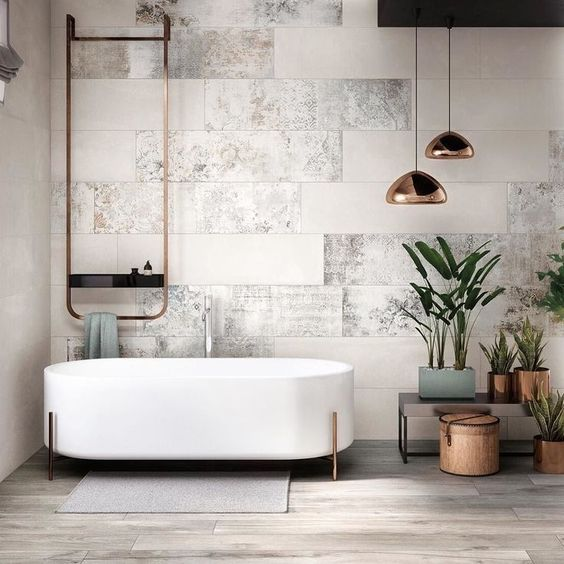 a chic modern space with neutral tiles, a free-standing bathtub on copper legs, copper lamps and fixtures
