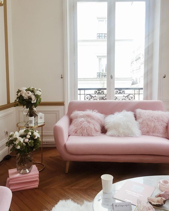 a pink sofa with faux fur pillows makes this space more playful and girlish