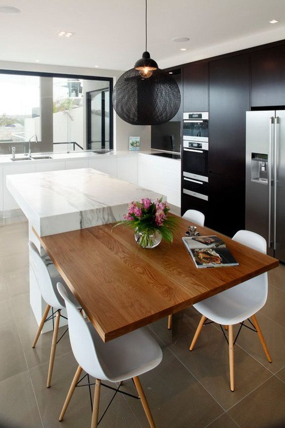 a black kitchen with a white marble kitchen island and an additional tabletop for having meals