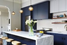 24 a chic modern space in cobalt blue and white looks very contrasting, a marble counter and wooden stools add interest