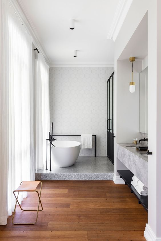 a chic space with geo tiles, grey bathtub floor, a concrete vanity, a black shower and wooden floors