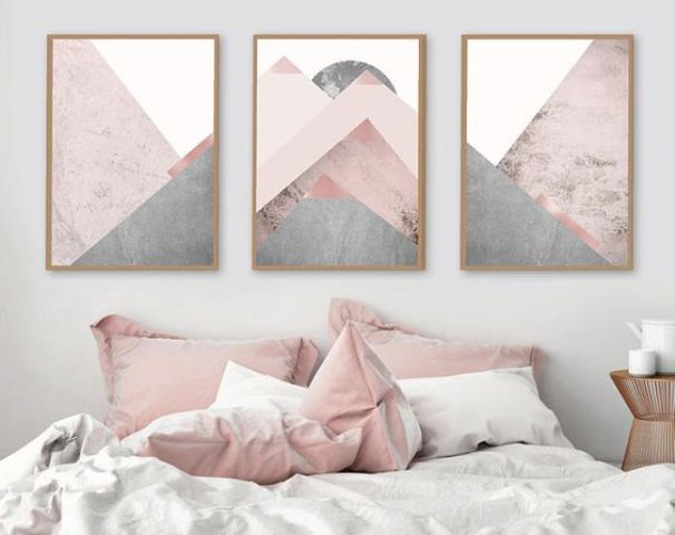 blush pillows and a geometric artwork with blush tones create a soft feel in the bedroom