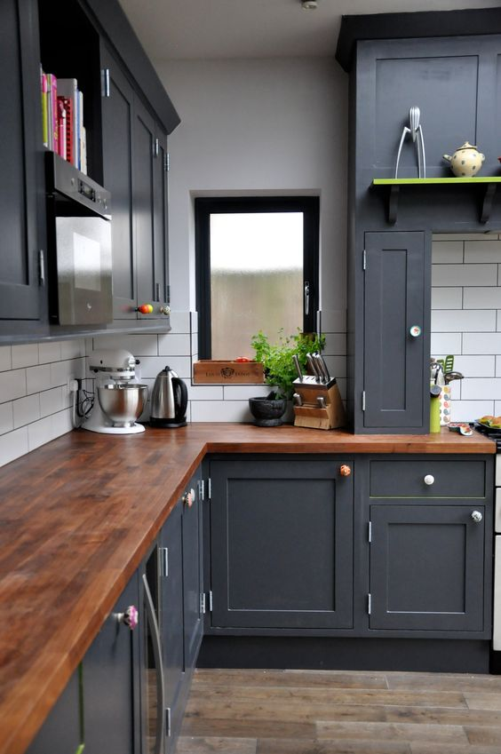 dark grey kitchen with wooden countertops of a saturated shade and metallic handles