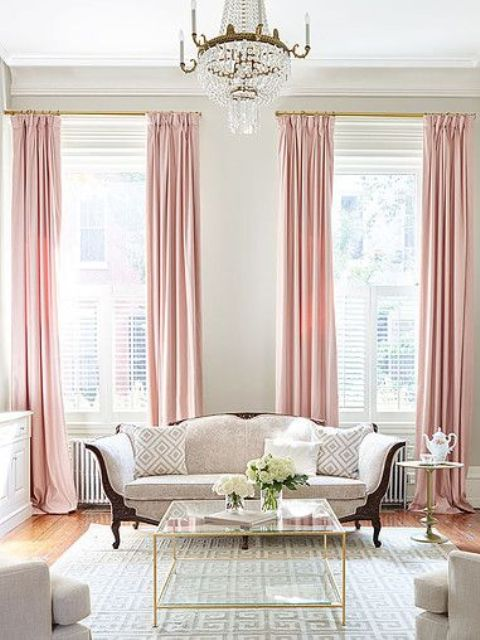 a chic living room with pink curtains and brass touches for a soft feel