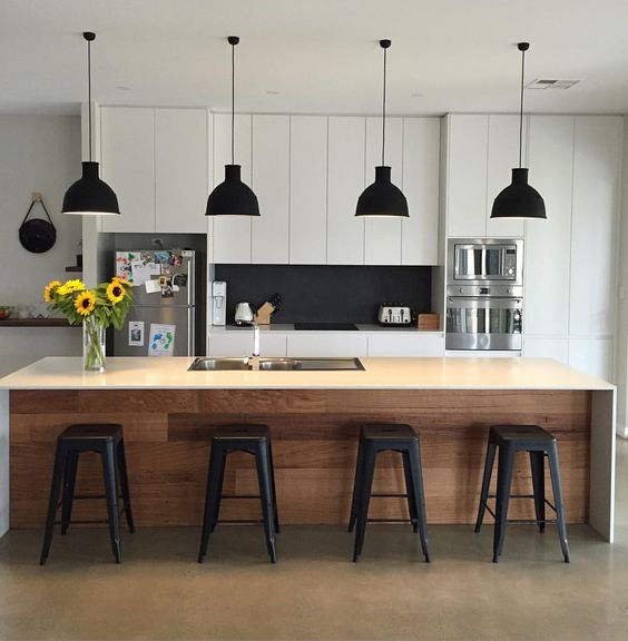 a modern black and white kitchen is spruced up with a wooden kitchen island