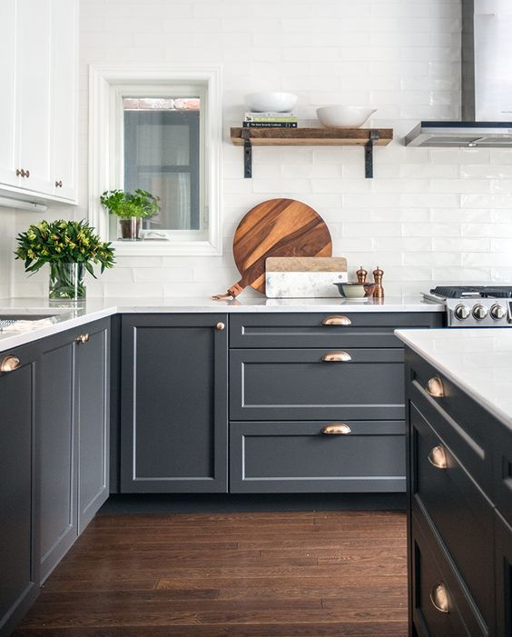 graphite grey cabinets are made more elegant with metallic handles and white tabletops