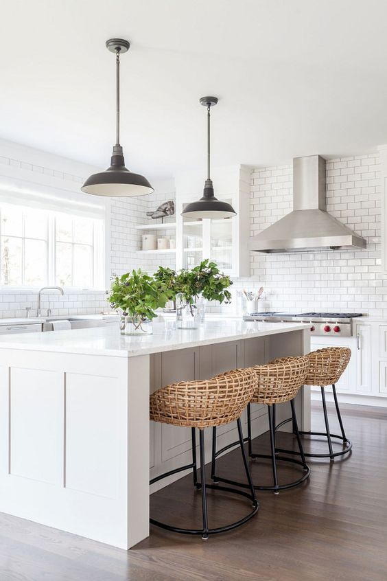 a chic white kitche with a functional kitchen island and woven stools