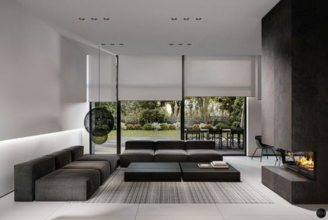 a modern moody space with dark furniture, a fireplace and black lamps