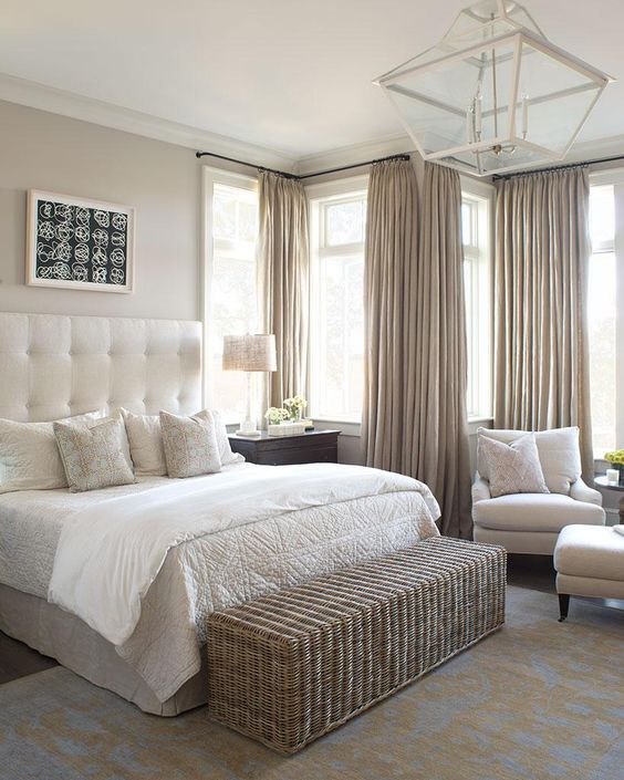 a neutral bedroom with a long wicker bench and storage space in one for a cozy feel