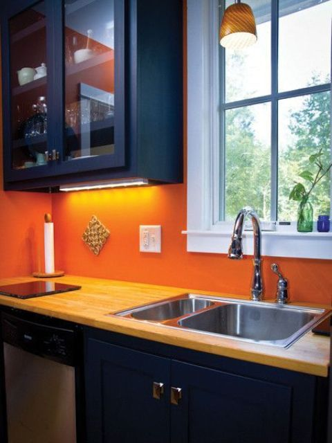 modern navy cabinets are accentuated with an orange backsplash and neutral wood countertops