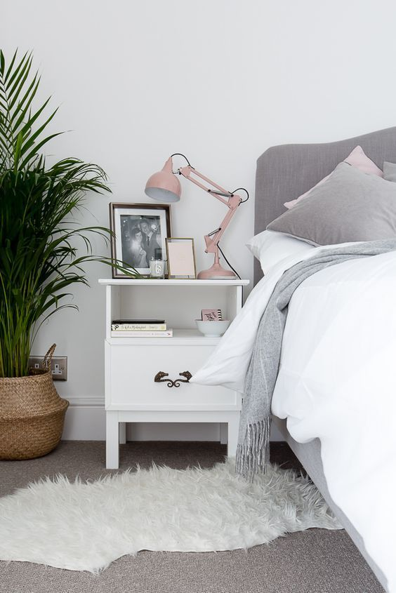 a blush lamp adds a cute colorful touch to the grey and white bedroom