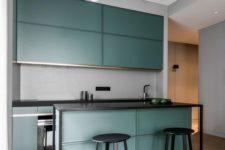 27 a modern dark green kitchen with black framing and a grey backsplash, small yet very stylish