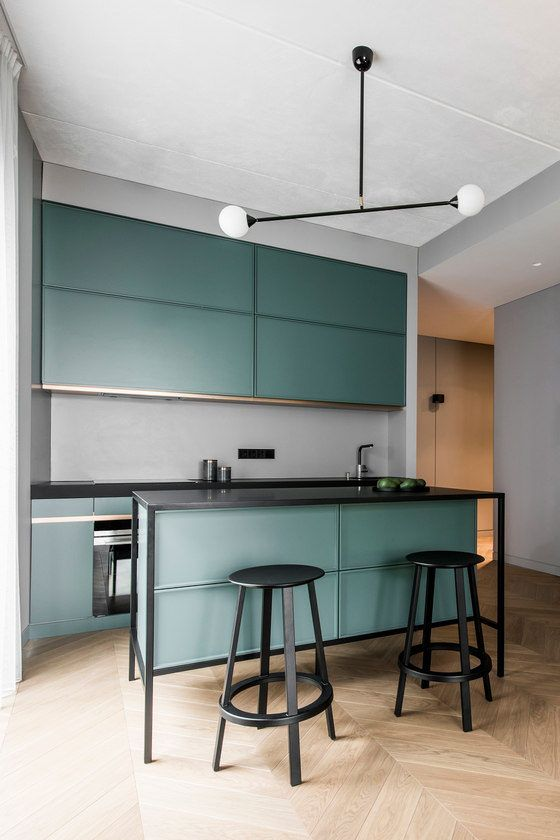 a modern dark green kitchen with black framing and a grey backsplash, small yet very stylish