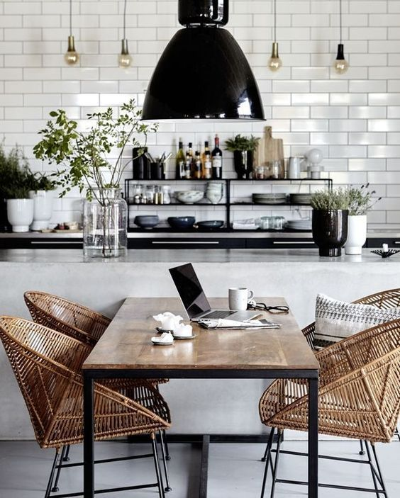 a modern monochrome kitchen with wicker chairs that soften the space and make it cozier