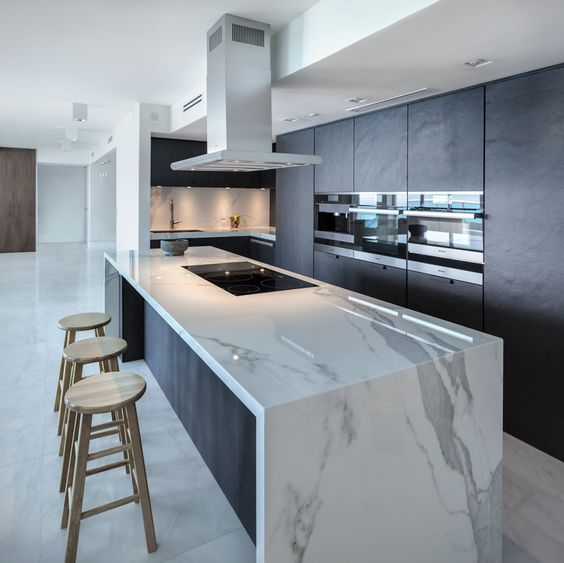 a minimalist dark kitchen with a gorgeous large white marble kitchen island for cooking and eating