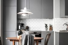 28 a modern grey kitchen with a subway tile backsplash and a wooden dining set for a contrast