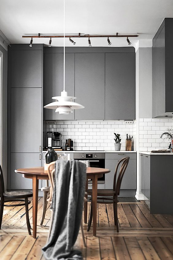 a modern grey kitchen with a subway tile backsplash and a wooden dining set for a contrast