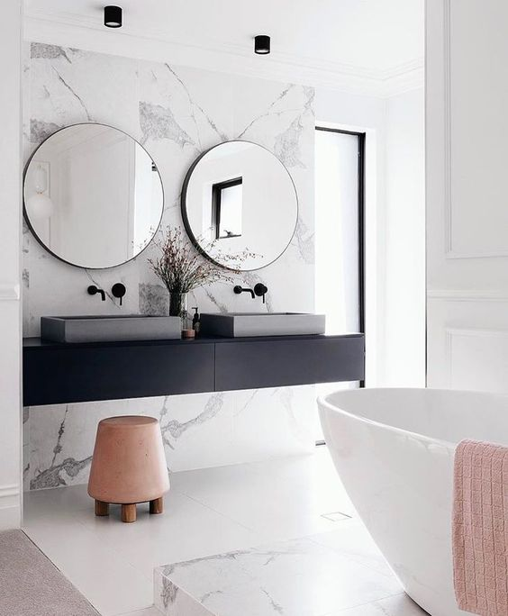 a modern space with white marble, a black vanity, a free-standing bathtub and concrete sinks looks chic