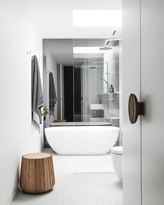 a modern white space with a free-standing tub, white fixtures and a wooden stool