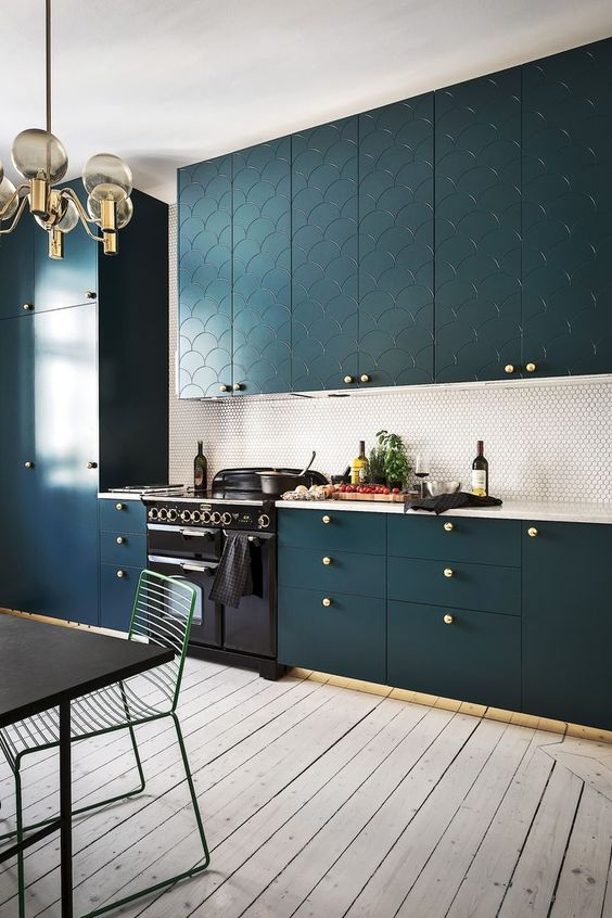 a teal kitchen with patterns, a penny tile backsplash and brass touches for a refined touch