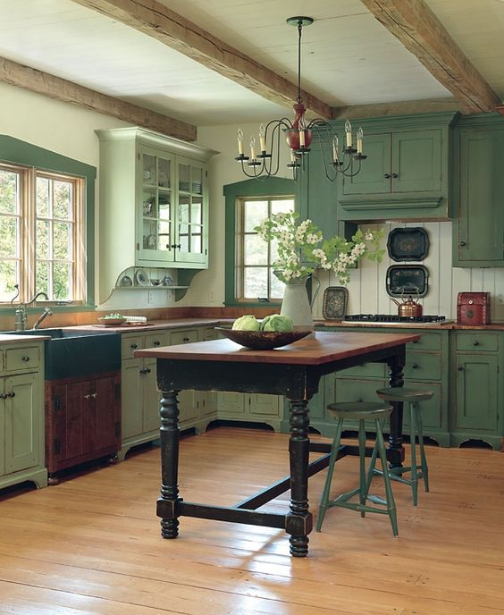 pale green vintage-kitchen is made cozier with wooden beams and an antique dining table