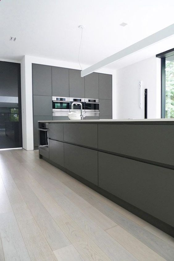 sleek minimalist grey kitchen with a large kitchen island and all the rest done in white for a fresh look