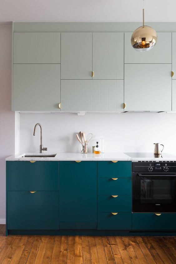 a teal and mint modern kitchen with a white backsplash and copper touches looks bold and chic