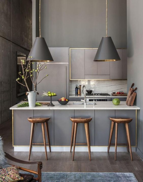a modern small kitchen with matte grey cabinets, white marble counters and a backsplash and matching lamps