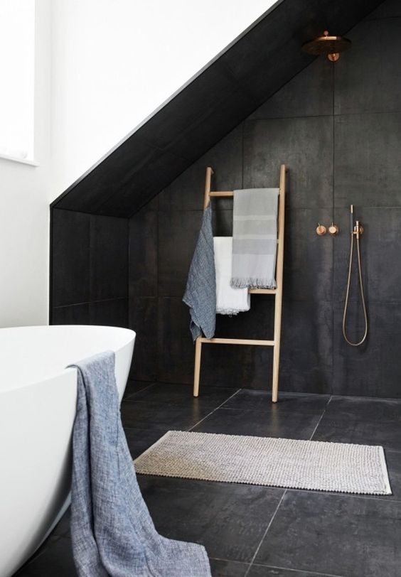 attic bathroom with attic accentuated with black tiles and some brass fixtures