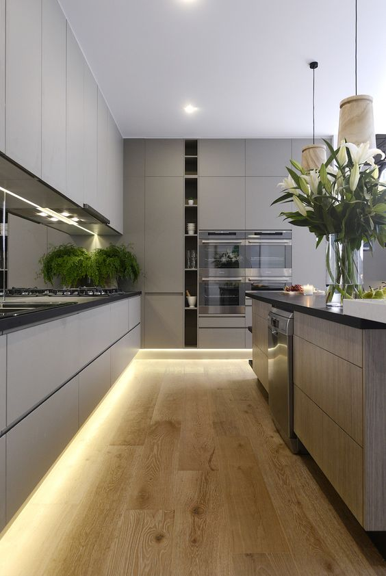 a stylish grey kitchen with lighting up, a vertical open shelf and a large kitchen island