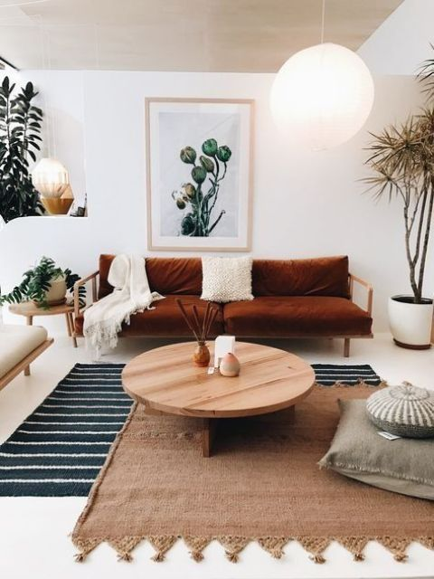 white and cream are taken as main colors, shades of brown and neutral wood add style and softness, and a burnt orange sofa is used for a colorful touch