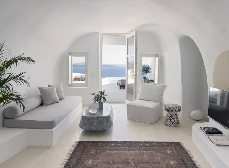 The living room in pure white features a platform sofa, a chair and an eye catchy stone table, a couple of windows with cool views