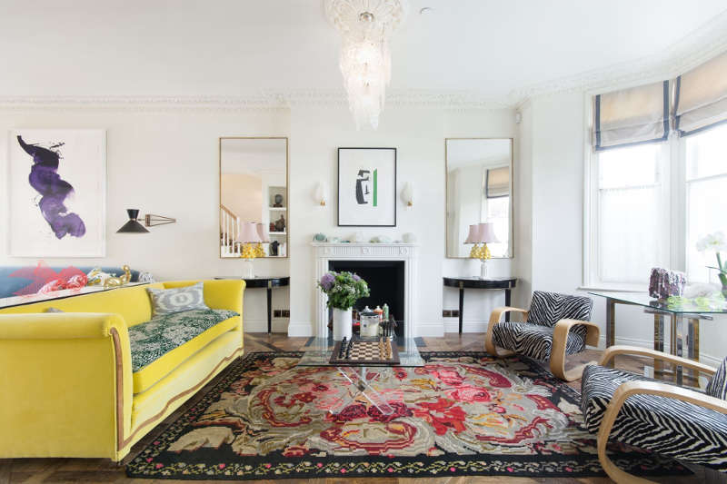 This gorgeous living room is done with a bold yellow sofa, animal print chairs, a gorgeous vintage chandelier and an antique fireplace