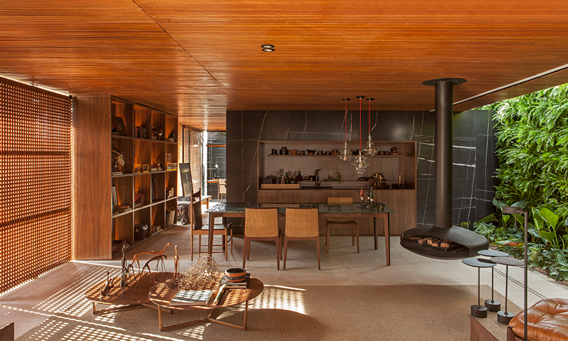 This gorgeous open layout is a part of a Brazilian home, done with wood, marble stone and in an earthy color palette