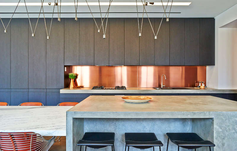 This is a kitchen in a luxurious Australian home, enjoy the look of the shiny copper backsplash that contrasts grey wood cabinets