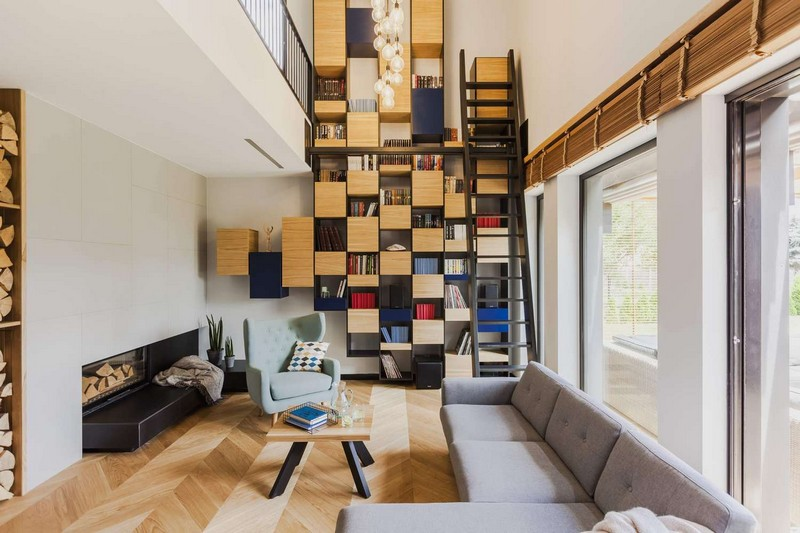 This modern and bold residence features a cool floor to ceiling bookcase and bold touches of blue throughout the interiors