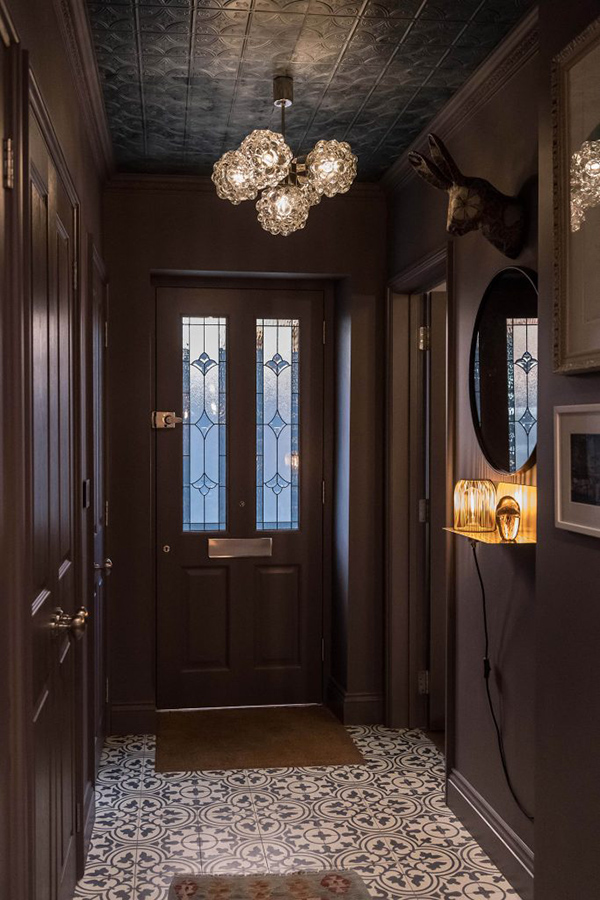 The entryway is done in dark shades, with a faux animal head and cool vintage lamps that hint on what's further