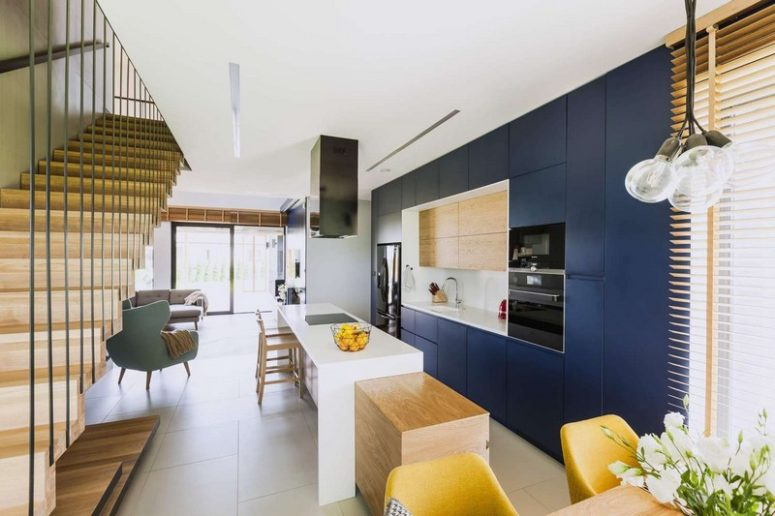 The kitchen is done with sleek navy cabinets, light-colored wood and a long kitchen island that features a breakfast zone
