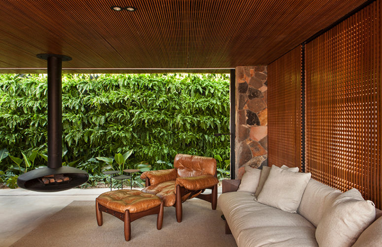 The living room features comfy contemporary furniture and a hanging fireplace, the space is opened to outdoors when necessary and there's a green wall