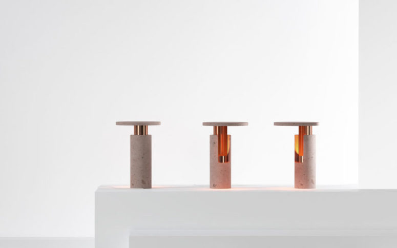 The table lamp features copper cylindrical interior and volcanic rock body in pink