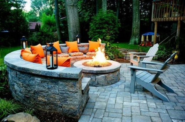a gorgeous firepit zone with a round stone bench, candle lanterns and orange pillows for a fall feel