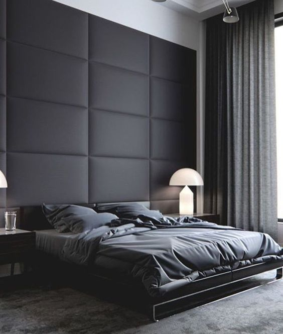 a moody masculine space with an upholstered black wall that brings softness and comfort to the room decor