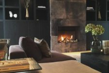 02 a refined moody living room with a built-in fireplace clad with dark metal looks wow
