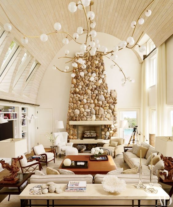 a stunning stone clad fireplace adds texture and makes this neutral space warmer