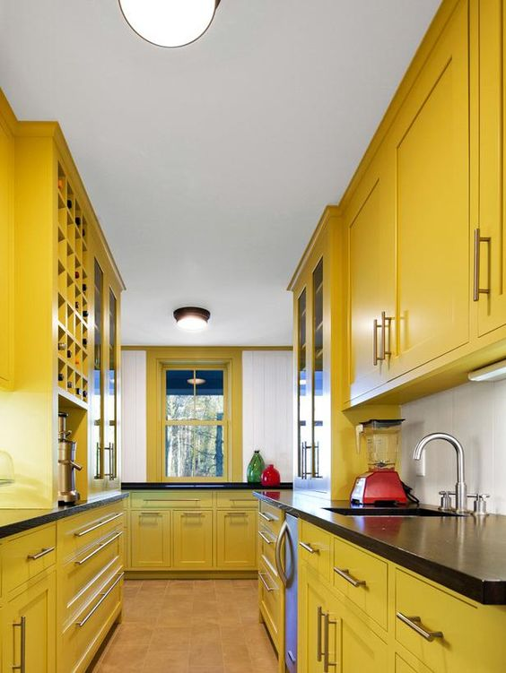 a vintage farmhouse yellow kitchen with black countertops is a bold solution