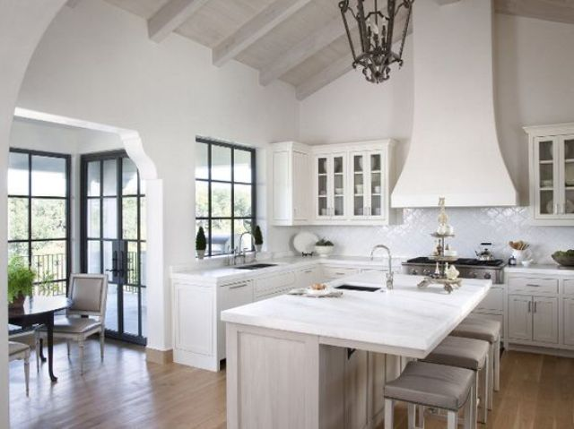 a white vintage farmhouse kitchen with a large hood, vintage lamps and a chic kitchen island
