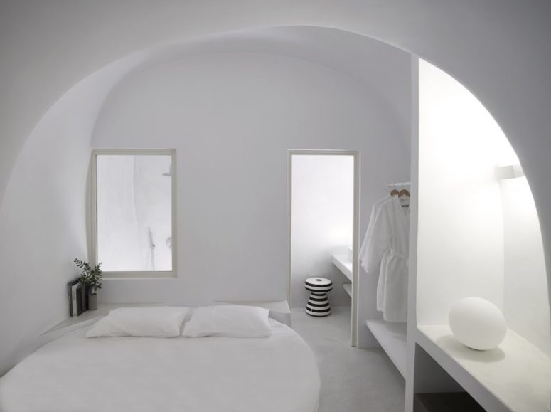 One of the bedrooms with a round bed, some built-in shelves and a bathroom enclosed