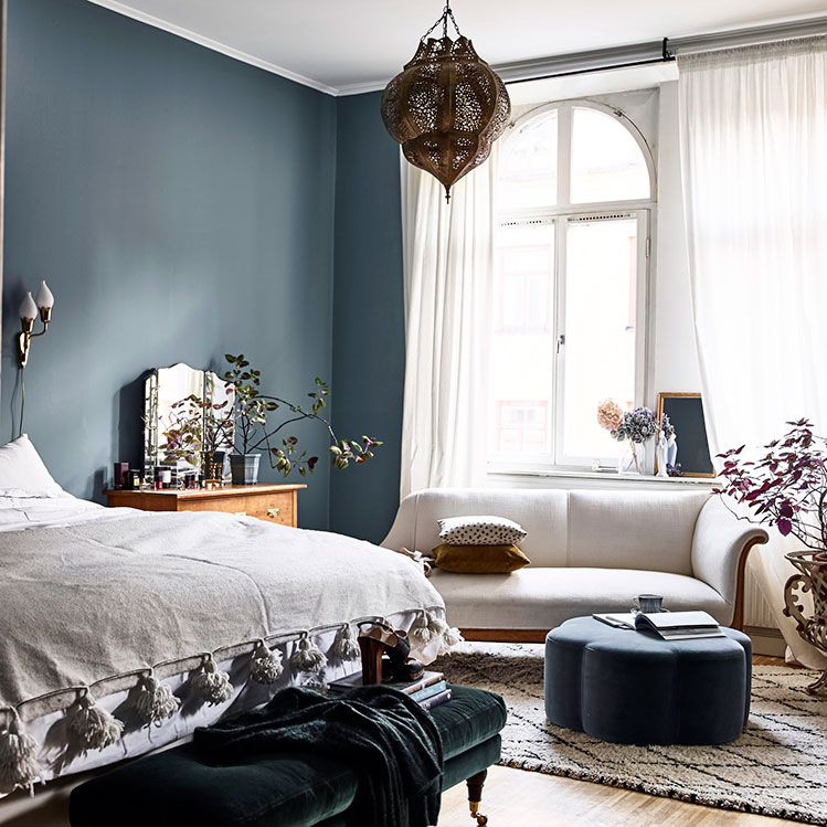 The bedroom is done in Scandinavian blue, with a Moroccan lamp like in the living room, some chic velvet furniture and vintage items