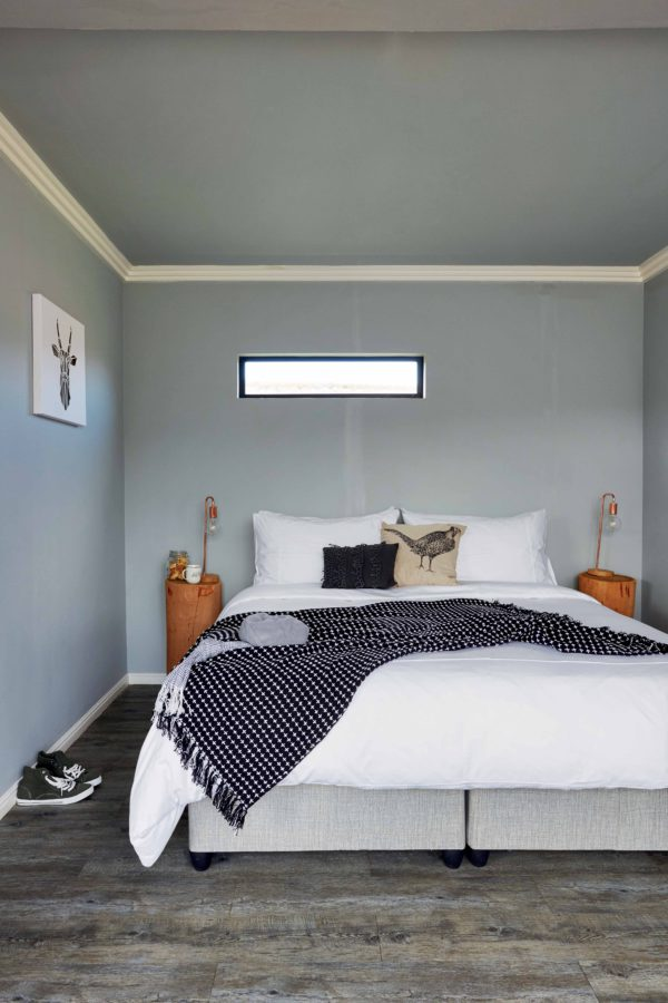The bedroom is small and simple, with a reclaimed wood floor, blue walls and ceiling and wooden stump nightstands with bulbs